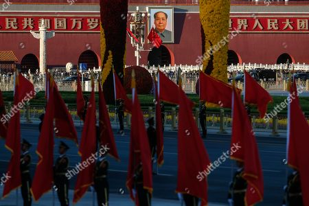 Members of the Chinese People's Liberation Army (PLA) honor guard stand in front of a portrait of Chairman Mao on the south gate of the Forbidden City as they hold flags in preparation for a welcome ceremony for Angolan president Joao Lourenco at the Great Hall of the People in Beijing, China, 09 October 2018.