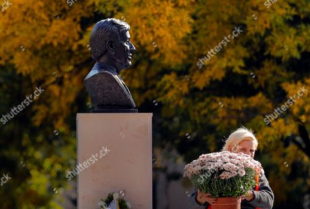 A municipal worker carries flowers next to the bust of Nobel laureate Elie Wiesel in Bucharest, Romania, . A bust of Romanian-born writer Elie Wiesel has been unveiled in Bucharest on the country's national Holocaust remembrance day. The director of Romania's National Institute for the Study of the Holocaust joined Bucharest's mayor and the U.S. and Israeli ambassadors on Tuesday for the event in a small square named after Wiesel in the capital