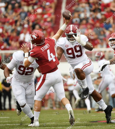 Stock Photo of Raekwon Davis, Quinnen Williams, Ty Storey. Alabama defenders Raekwon Davis (99) and Quinnen Williams (92) put pressure on Arkansas quarterback Ty Storey in the first half of an NCAA college football game, in Fayetteville, Ark