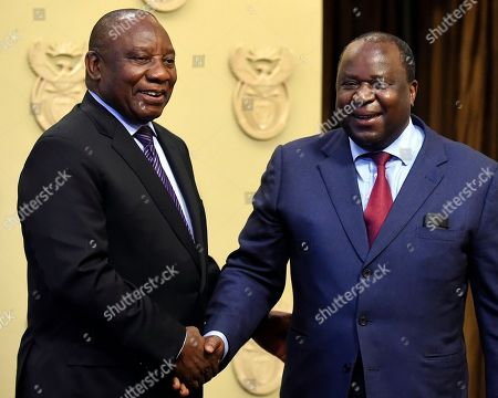 South African President Cyril Ramaphosa, left, shakes hand with newly elected Finance Minister, Tito Mboweni, in Cape Town, South Africa, Tuesday, Oct.9 2018. Former finance minister Nhlanhla Nene resigned after acknowledging missteps during the scandal-tainted tenure of former president Jacob Zuma
