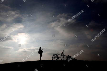 A young woman takes pictures as the sun sets above the Olympic Park in Munich, Germany