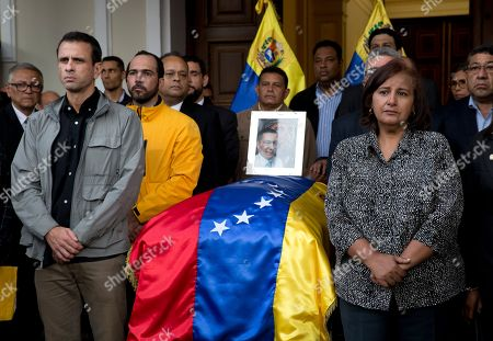 Dinorah Figuera, Henrique Capriles. Opposition leader Henrique Capriles, left, and lawmaker Dinorah Figuera, stand vigil around the flag-draped casket containing the remains of opposition activist Fernando Alban, during a solemn ceremony at the National Assembly headquarters, in Caracas, Venezuela, . International condemnation of Venezuela's leadership poured in Tuesday following the suspicious death of Alban authorities say evaded justice by throwing himself from the 10th floor of a police building