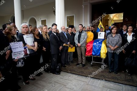 Henrique Capriles, Dinorah Figuera. Opposition leader Henrique Capriles, left center, and lawmaker Dinorah Figuera, stand vigil around the flag-draped casket containing the remains of opposition activist Fernando Alban, during a solemn ceremony at the National Assembly headquarters, in Caracas, Venezuela, . International condemnation of Venezuela's leadership poured in Tuesday following the suspicious death of Alban authorities say evaded justice by throwing himself from the 10th floor of a police building