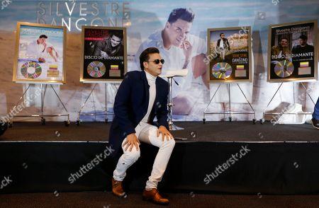 "Colombian singer Silvestre Dangond watches a video of his last production during a press conference in Bogota, Colombia, . The star of vallenato received five diamond selling records on Tuesday, for ""Esto es vida"", ""Sigo invicto"", ""No me compares con nadie"", ""El original"" and ""Gente Valiente"