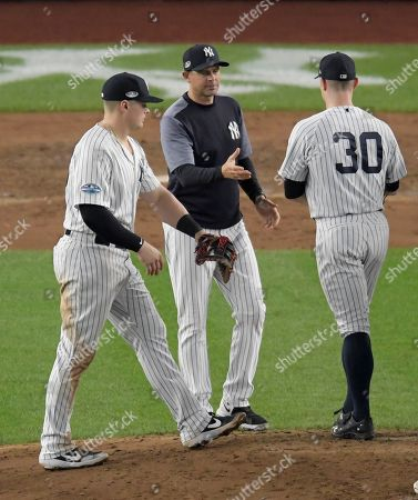 New York Yankees manager Aaron Boone, center, takes the ball from relief pitcher David Robertson (30) during the seventh inning of Game 4 of baseball's American League Division Series against the Boston Red Sox, in New York