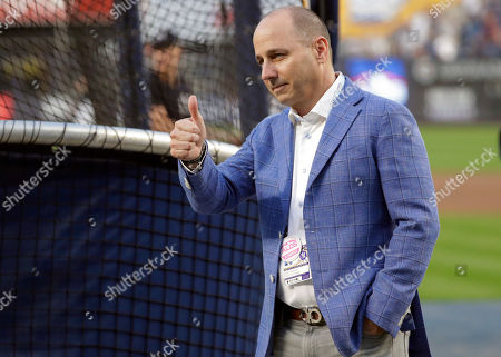 Stock Image of New York Yankees general manager Brian Cashman gestures to fans as his team warms up before Game 4 of a baseball American League Division Series against the Boston Red Sox, in New York
