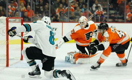 San Jose Sharks' Joe Pavelski (8), left, scores against Philadelphia Flyers' Brian Elliott, center, and Andrew MacDonald, right, during the first period an NHL hockey game, in Philadelphia