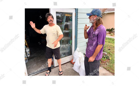 Dwight Williams, left, and Timothy Thomas discuss whether to evacuate their neighborhood in Panama City Beach, Fla., on . Thomas figures he and his wife will be safe from rising ocean water since they live in a second-story apartment. Others also aren't leaving, and a bar along the beachfront road threw a hurricane party less than 2 miles away from Thomas' home as Michael pushed toward shore Tuesday night