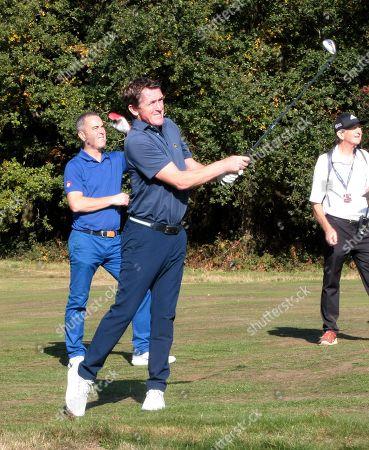 Tony McCoy swings, watched by James Nesbitt