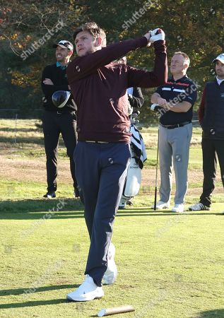 Niall Horan drives on the 11th hole watched by Charl Schwartzel at the Pro-Am