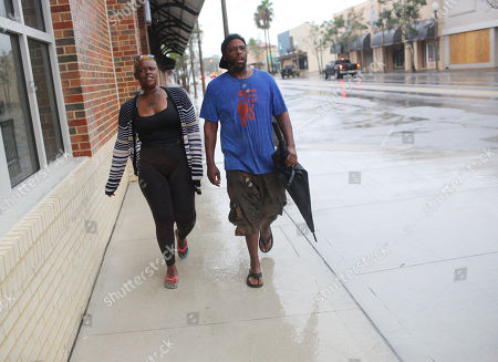 Sarah Scott (L) and Shawn Glasper walks through the streets as Hurricane Michael begins to make landfall in Panama City, Florida USA, 10 October 2018. Reports state that more than 370,000 people in Florida have been ordered to evacuate their homes and move safer locations.