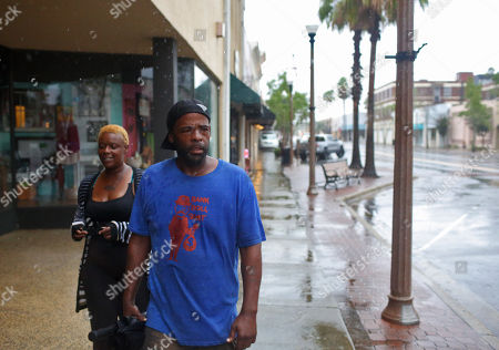 Stock Image of Sarah Scott (L) and Shawn Glasper walks through the streets as Hurricane Michael begins to make landfall in Panama City, Florida USA, 10 October 2018. Reports state that more than 370,000 people in Florida have been ordered to evacuate their homes and move safer locations.