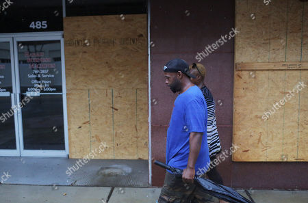 Shawn Glasper (L) and Sarah Scott walk by boarded up shops as Hurricane Michael begins to make landfall in Panama City, Florida USA, 10 October 2018. Reports state that more than 370,000 people in Florida have been ordered to evacuate their homes and move safer locations.