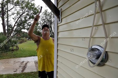 Stock Image of Luke Ford finishes nailing some boards to the outside of a home before evacuating, in Keaton Beach, Fla. Hurricane Michael continues to churn in the Gulf of Mexico heading for the Florida panhandle