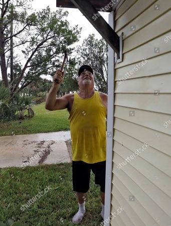 Stock Photo of Luke Ford finishes nailing some boards to the outside of a home before evacuating, in Keaton Beach, Fla. Hurricane Michael continues to churn in the Gulf of Mexico heading for the Florida panhandle