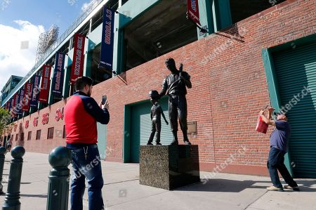 Stock Picture of Pedestrians take photos of a statue of Boston Red Sox legend Ted Williams outside Fenway Park, in Boston. Game 1 of the baseball American League Championship Series between the Red Sox and the Houston Astros is scheduled for Saturday in Boston