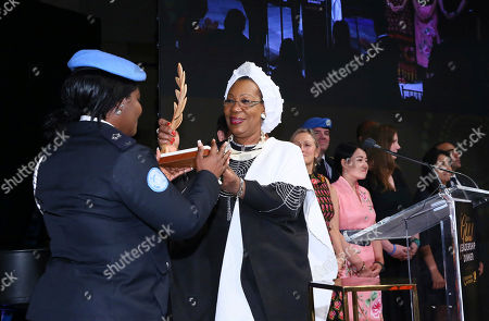 Catherine Samba-Panza, former and first female President of the Central African Republic, right, presents the United Nations Foundation's Global Leadership Award to U.N. Peacekeepers, accepted by U.N. Peacekeeper Fanny Aboagye from Ghana, for 70 years of service and sacrifice to advance peace, at the 2018 Global Leadership Awards Dinner on in New York. The dinner recognizes leaders who have helped tackle the world's most pressing challenges