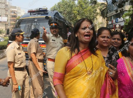 A police officer tries to prevent traffic blockade as activists of Congress party's women's wing shout slogans against Bollywood actor Nana Patekar during a protest in support of former Bollywood actress Tanushree Dutta in Mumbai, India, Thursday, Oct.11, 2018. A social media storm began in September, when Dutta spoke to several Indian TV news channels about her frustration with nothing resulting from a police complaint she filed in 2008 against Patekar for alleged sexual harassment on a Mumbai movie set. The complaint by the retired actress living in the United States could be a tipping point for the country's burgeoning #metoo movement