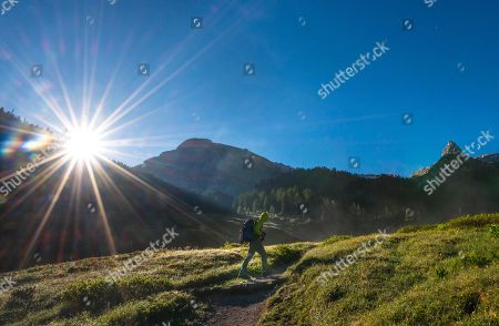 MODEL RELEASED Hiker in the morning sun, hiking trail to Wasseralm via Niederbrunnsulzen, Berchtesgaden National Park, Bavaria, Germany