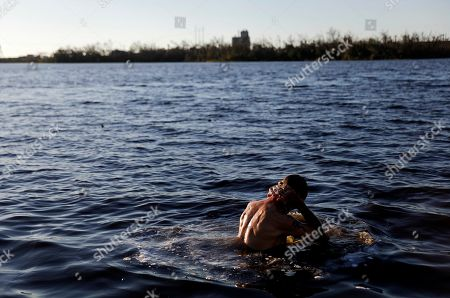 """John Bird bathes in a lake after working all day to repair his damaged townhouse which has no running water in the aftermath of hurricane Michael in Parker, Fla., . """"Power I can do without,"""" said Bird. """"Water is another thing"""