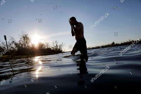 """John Bird emerges from bathing in a lake after working all day to repair his damaged townhouse which has no running water in the aftermath of hurricane Michael in Parker, Fla., . """"Power I can do without,"""" said Bird. """"Water is another thing"""