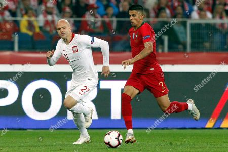 Poland's Rafal Kurzawa, left, and Portugal's Joao Cancelo vie for the ball during the UEFA Nations League soccer match between Poland and Portugal at the Silesian Stadium Chorzow, Poland