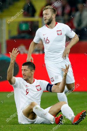 Poland's Robert Lewandowski, sitting, gestures during the UEFA Nations League soccer match between Poland and Portugal at the Silesian Stadium Chorzow, Poland, . At right is Poland's Jakub Blaszczykowski