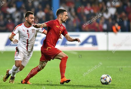 Montenegro's Marko Vesovic, center, and Serbia's Andrija Zivkovic run for the ball during the UEFA Nations League soccer match between Montenegro and Serbia at the City stadium in Podgorica, Montenegro