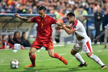 Montenegro's Marko Vesovic, left, duels for the ball with Serbia's Andrija Zivkovic during the UEFA Nations League soccer match between Montenegro and Serbia at the City stadium in Podgorica, Montenegro