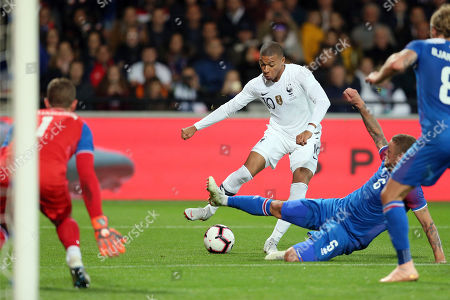 France's Kylian Mbappe, center, kicks the ball past Iceland's Ragnar Sigurdsson, during a friendly soccer match between France and Iceland, in Guingamp, western France