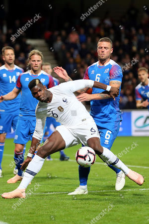 France's Paul Pogba, foreground, challenges for the ball with Iceland's Ragnar Sigurdsson, during a friendly soccer match between France and Iceland, in Guingamp, western France