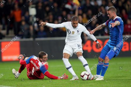 France's Kylian Mbappe, center, challenges for the ball with Iceland's goalkeeper Hannes Halldorsson, left, and Ragnar Sigurdsson, right, during a friendly soccer match between France and Iceland, in Guingamp, western France