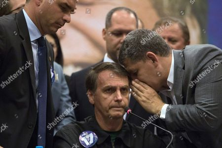 Gustavo Bebianno Rocha, right, president of the right wing Social Liberal Party, whispers to his presidential candidate Jair Bolsonaro, of the Social Liberal Party as his son Flavio Bolsonaro, left, stands aside during a press conference in Rio de Janeiro, Brazil, . Bolsonaro will face Workers Party presidential candidate Fernando Haddad in a presidential runoff on Oct. 28