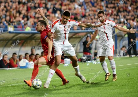 Montenegrian's Marko Vesovic (L) in action against Serbia's Aleksandar Mitrovic (C) and  Andrija Zivkovic (R) during the UEFA Nations League match between Montenegro and Serbia in Podgorica, Montenegro, 11 October 2018.