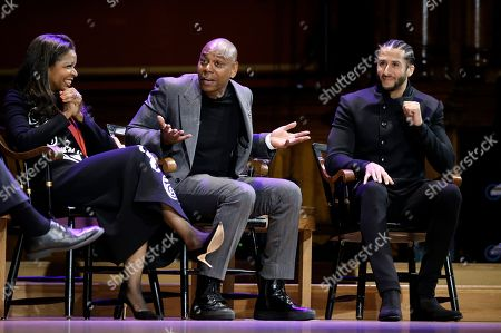 Stock Image of Comedian Dave Chappelle, center, shares a light moment with philanthropist Pamela Joyner, left, and former NFL quarterback Colin Kaepernick, right, on stage during W.E.B. Du Bois Medal award ceremonies, at Harvard University, in Cambridge, Mass. Joyner, Chappelle, and Kaepernick are among eight recipients of Harvard University's W.E.B. Du Bois Medals in 2018. Harvard has awarded the medal since 2000 to people whose work has contributed to African and African-American culture