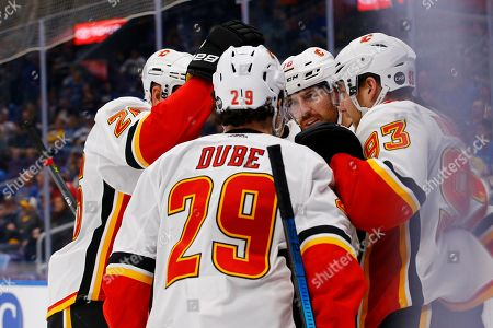 Calgary Flames' James Neal (18) is congratulated by Michael Stone (26), Dillon Dube (29), and Sam Bennett (93) after scoring a goal during the first period of the team's NHL hockey game against the St. Louis Blues, in St. Louis