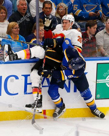 Calgary Flames' Michael Stone, top left, is upended as he is checked into the boards by St. Louis Blues' Joel Edmundson during the third period of an NHL hockey game, in St. Louis. The Blues won 5-3