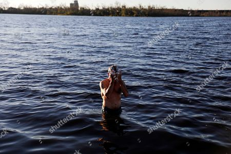 """Stock Photo of John Bird bathes in a lake after working all day to repair his damaged townhouse which has no running water in the aftermath of hurricane Michael in Parker, Fla., . """"Power I can do without,"""" said Bird. """"Water is another thing"""