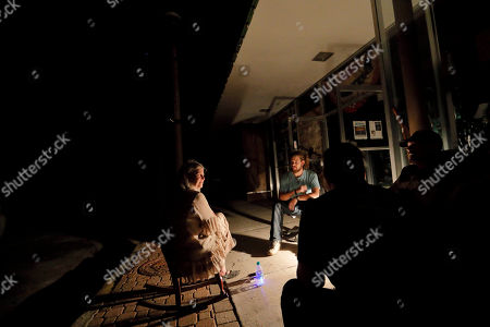 Jane Lindsey, left, sits by a lantern outside her antique shop with her grandson Cody Weaver, from left, son-in-law Chris Allen and daughter Amy Lindsey during a power outage in the aftermath of hurricane Michael in Panama City, Fla