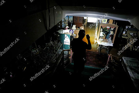 Chris Allen looks into the flooded lower level of an antique shop during a power outage in the aftermath of hurricane Michael in Panama City, Fla