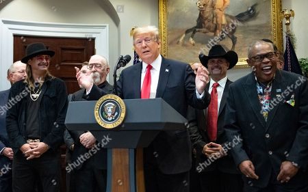 "United States President Donald Trump makes remarks prior to signing H.R. 1551, the 'Orrin G. Hatch-Bob Goodlatte Music Modernization Act' in the Roosevelt Room of the White House Pictured behind the President from left to right: Kid Rock, guitarist Jeff ""Skunk"" Baxter, John Rich of Big & Rich, and Soul legend Sam Moore of Sam & Dave."