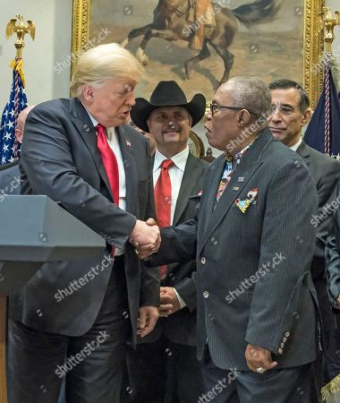 United States President Donald Trump, left, shakes hands with Soul legend Sam Moore of Sam & Dave, right center, prior to signing H.R. 1551, the 'Orrin G. Hatch-Bob Goodlatte Music Modernization Act' in the Roosevelt Room of the White House Looking on are John Rich of Big & Rich, left center, and US Representative Darrell Issa (Republican of California), right.