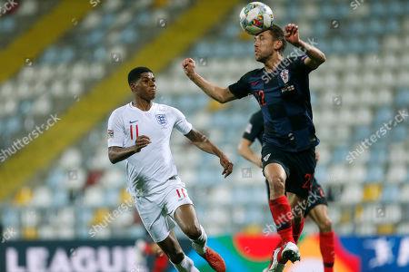 Croatia's Josip Pivaric heads the ball before England's Marcus Rashford during the UEFA Nations League soccer match between Croatia and England at Rujevica stadium in Rijeka, Croatia