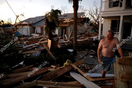 """Stock Photo of Dave Mullins looks out over the damage in front of his home, seen in background left, where he rode out hurricane Michael in Mexico Beach, Fla., . """"Right now I just need communication,"""" said Mullins of not having cell phone service. """"If I can get out here I would"""
