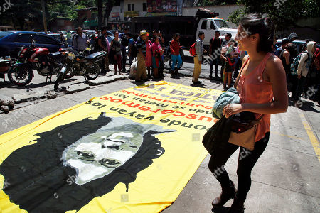 Lura Zuniga Caceres, daughter of prize-winning Honduran indigenous and environmental rights activist Berta Caceres, walks past a banner with the image of her mother outside the prosecutor's office in Tegucigalpa, Honduras, . Berta's daughters are demanding Honduras' Attorney General Oscar Chinchilla add more charges to their mother's murder case, after the supreme court indefinitely suspended the start of a trial on Sept. 17, of eight men charged in her 2016 killing