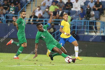Brazil's Neymar (R) fights for the ball against Saudi Arabia's Omar Hawsawi (C) during the friendly international soccer match between Saudi Arabia and Brazil, in Riyadh, Saudi Arabia, 12 October 2018.