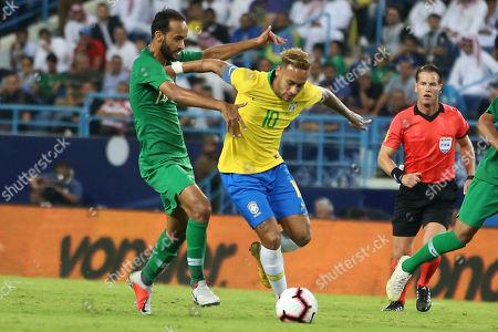 Brazil's Neymar (C) fights for the ball against Saudi Arabia's Abdullah Otayf (L) during the friendly international soccer match between Saudi Arabia and Brazil, in Riyadh, Saudi Arabia, 12 October 2018.