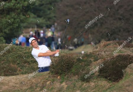 Ross Fisher, from Surrey, plays his recovery shot in the heather at 15th hole