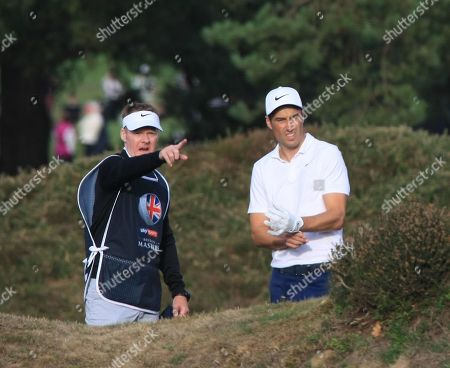 Ross Fisher, local lad from Surrey, and his caddy asses the shot in the heather at 15th hole