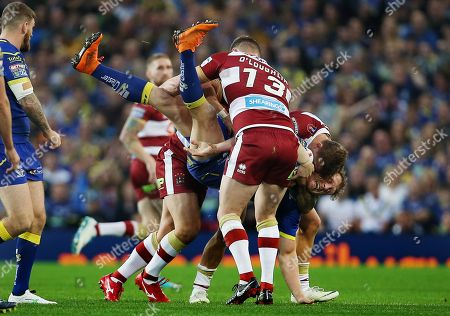 Ben Westwood of Warrington Wolves is tackled by Sean O'Loughin of Wigan Warriors